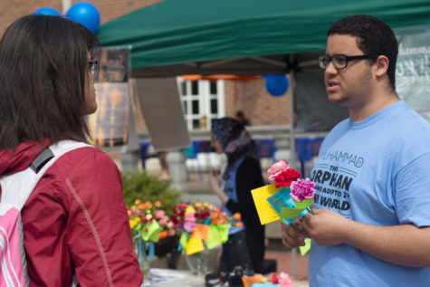 "Aly Taha, sophomore in Business, gives a flower to Kayla Smith, senior in LAS, as he explains the significance of Muhammad during the ""Muhammad: The Orphan Who Adopted the World"" event on the Main Quad on Wednesday."