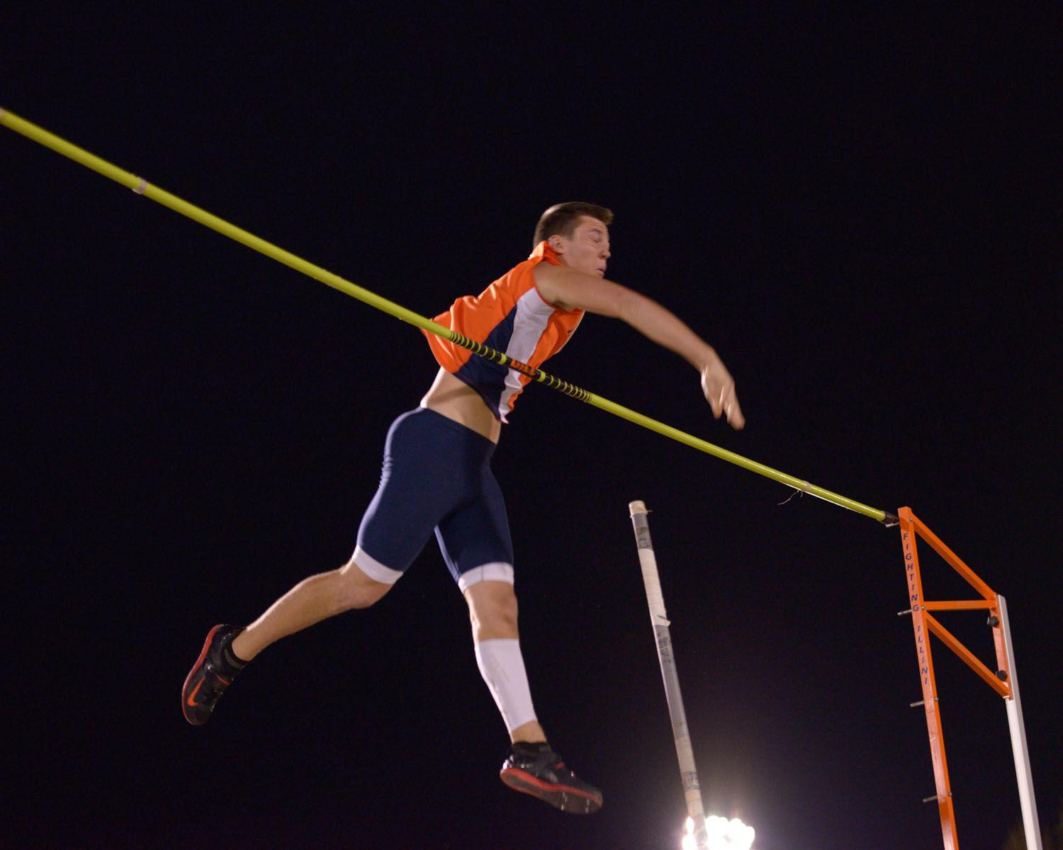 Illinois' Mitch Mammoser releases the pole as he swings over the bar during the poll vault event at the Illinois Twilight Meet.
