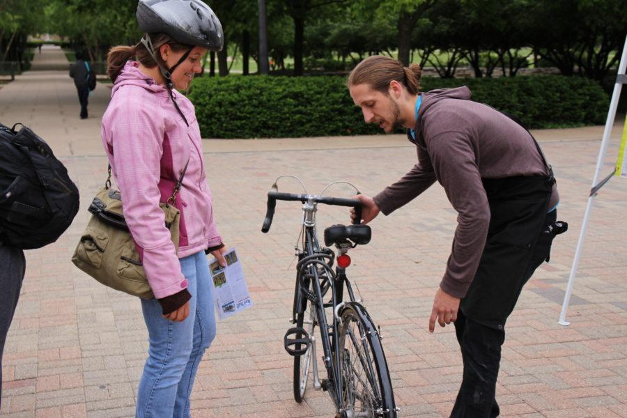 Matt Crosby, shop manager of Neutral Cycle, checks Bethany Carrol's, Champaign County Regional Planning Commission member, biketires during Bike to Work Day on the Engineering Quad.