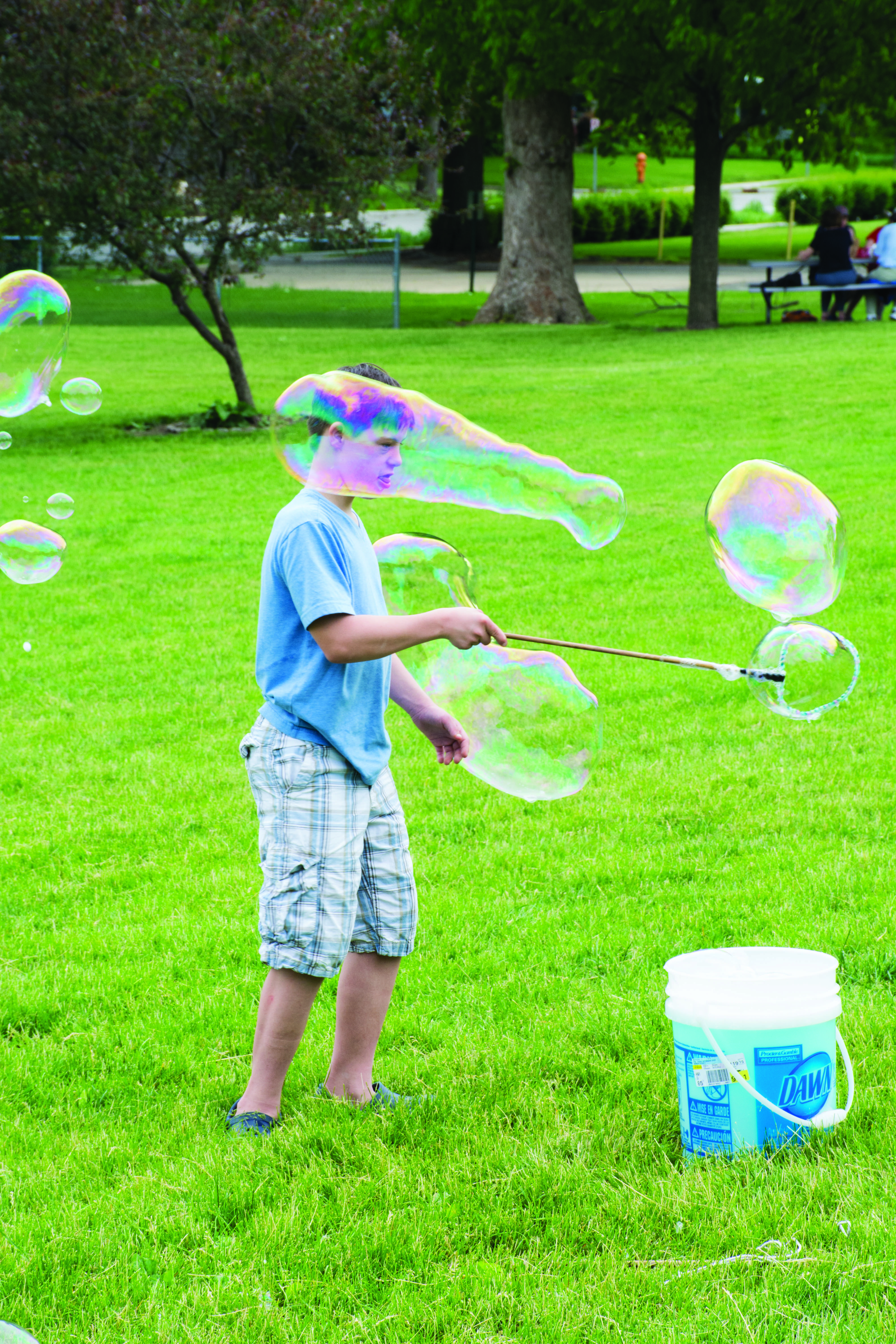 Hagen Barker, 13, a former South Side Elementary School student, makes bubbles at the 90th anniversary celebration.