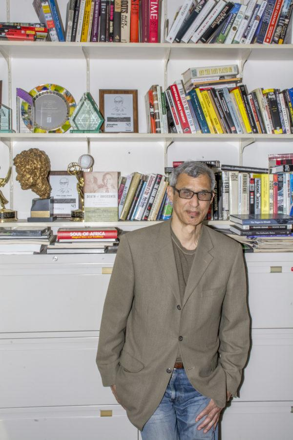 Chris Benson, professor in Media and award-winning author, stands in his office surrounded by books, including a copy of his own,
