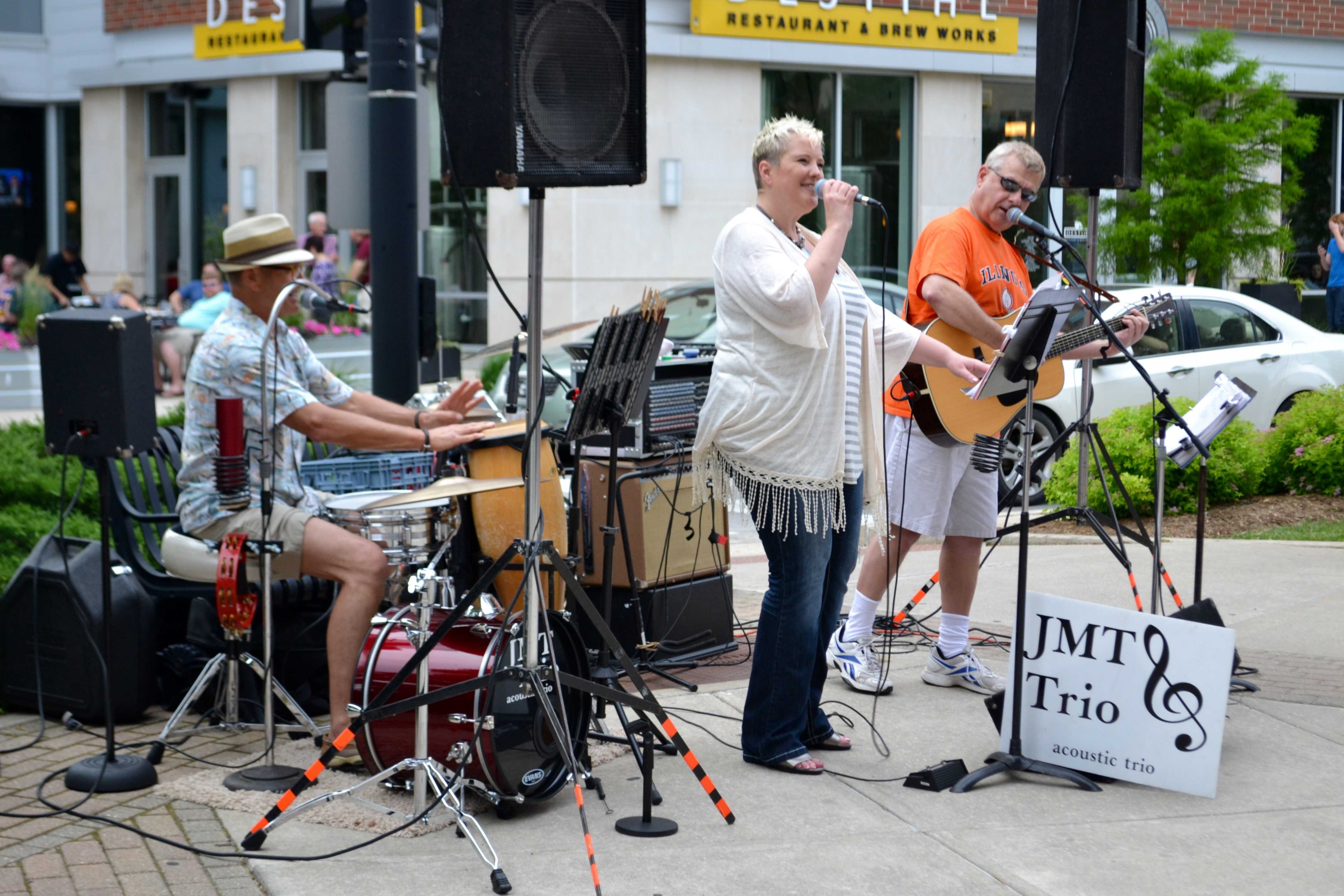 JMT Trio, a country, pop and oldies band, performs for a large crowd in Downtown Champaign during Friday Night Live on Friday, May 29.