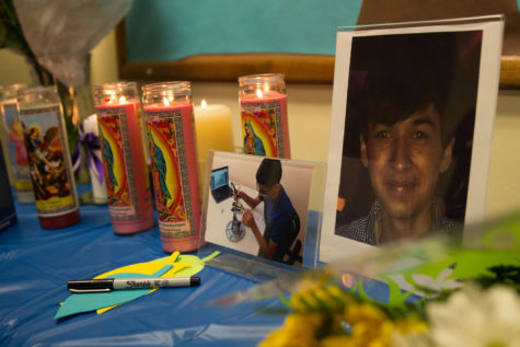 A picture of Vicente Mundo sits next to candles placed on a table during a vigil for Mundo at the La Casa Cultural Latina on Monday.