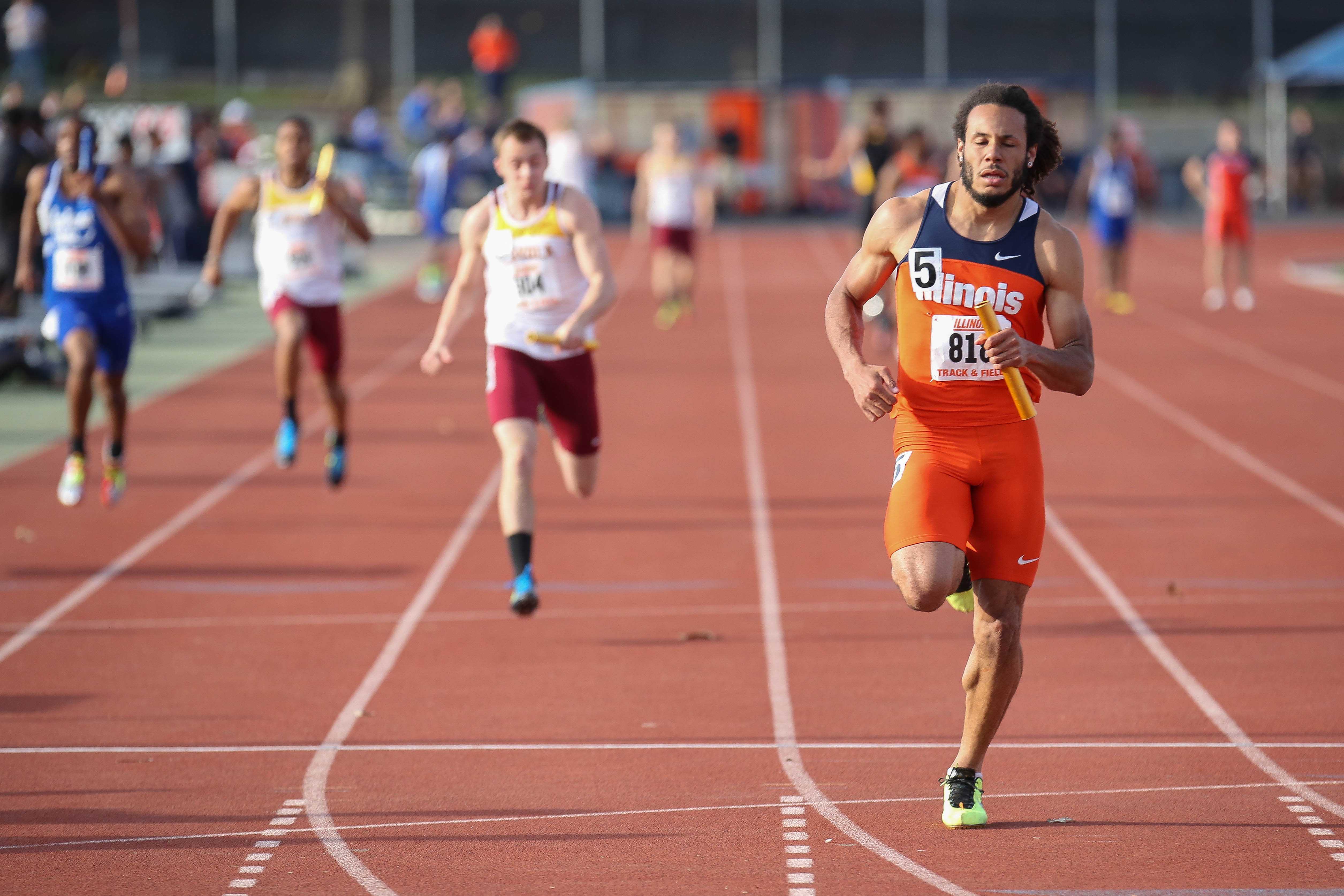 Illinois' DJ Zhan crosses the finish line to win the 4x100 meter relay during the Illinois Twilight Track and Field meet at Illinois Soccer and Track Stadium on Saturday, April 12, 2014.