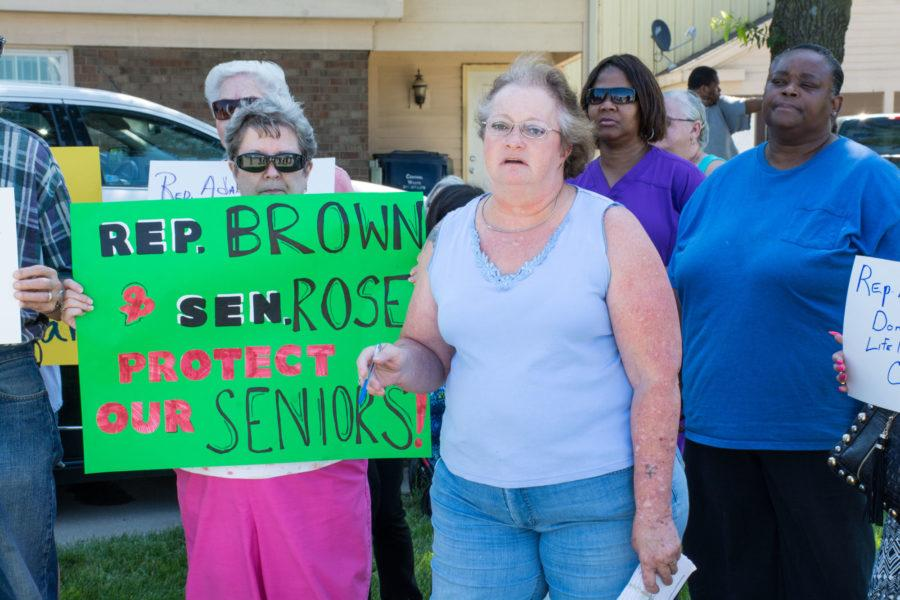 Local seniors along with Champaign County Health Care Consumers and the Illinois Alliance for Retired Americans rally in front of Rep. Adam Brown's and Sen. Chapin Rose's district offices in Champaign on Tuesday, July 14, to raise awareness about the effects of the proposed budget cuts to heating and cooling assistance and home care services.