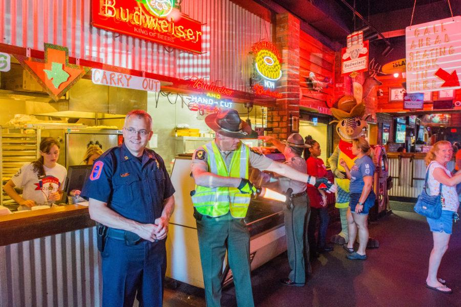 Officers from the Champaign Police Department, University of Illinois Police Department and Illinois State Troopers opened doors, directed traffic, and served food to help during the Special Olympics Illinois benefit lunch at Texas Roadhouse in Champaign on Friday, July 31.