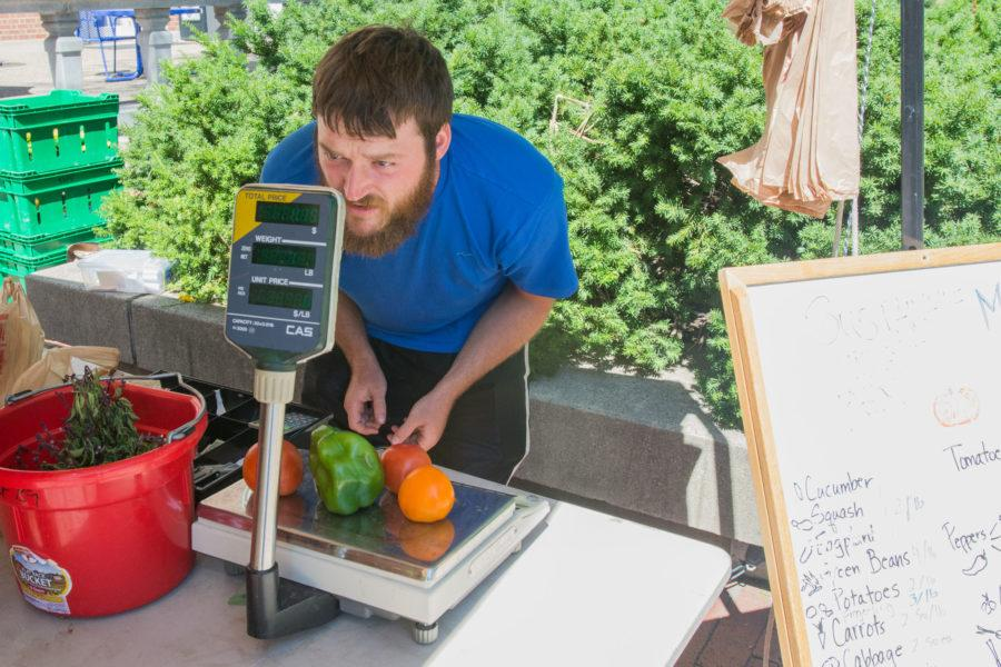 Chris Adair weighs vegetables at the farmers market in the Main Quad on Thursday, July 30.