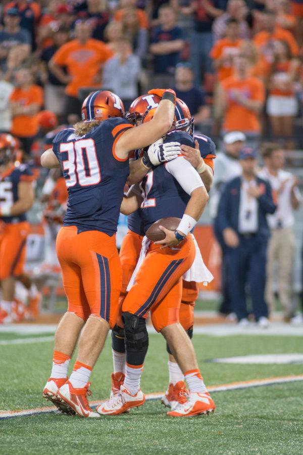 Wes Lunt (12), Jim Nudera (30), and another player celebrate after a successful play in Illinois' game vs. Middle Tennessee.