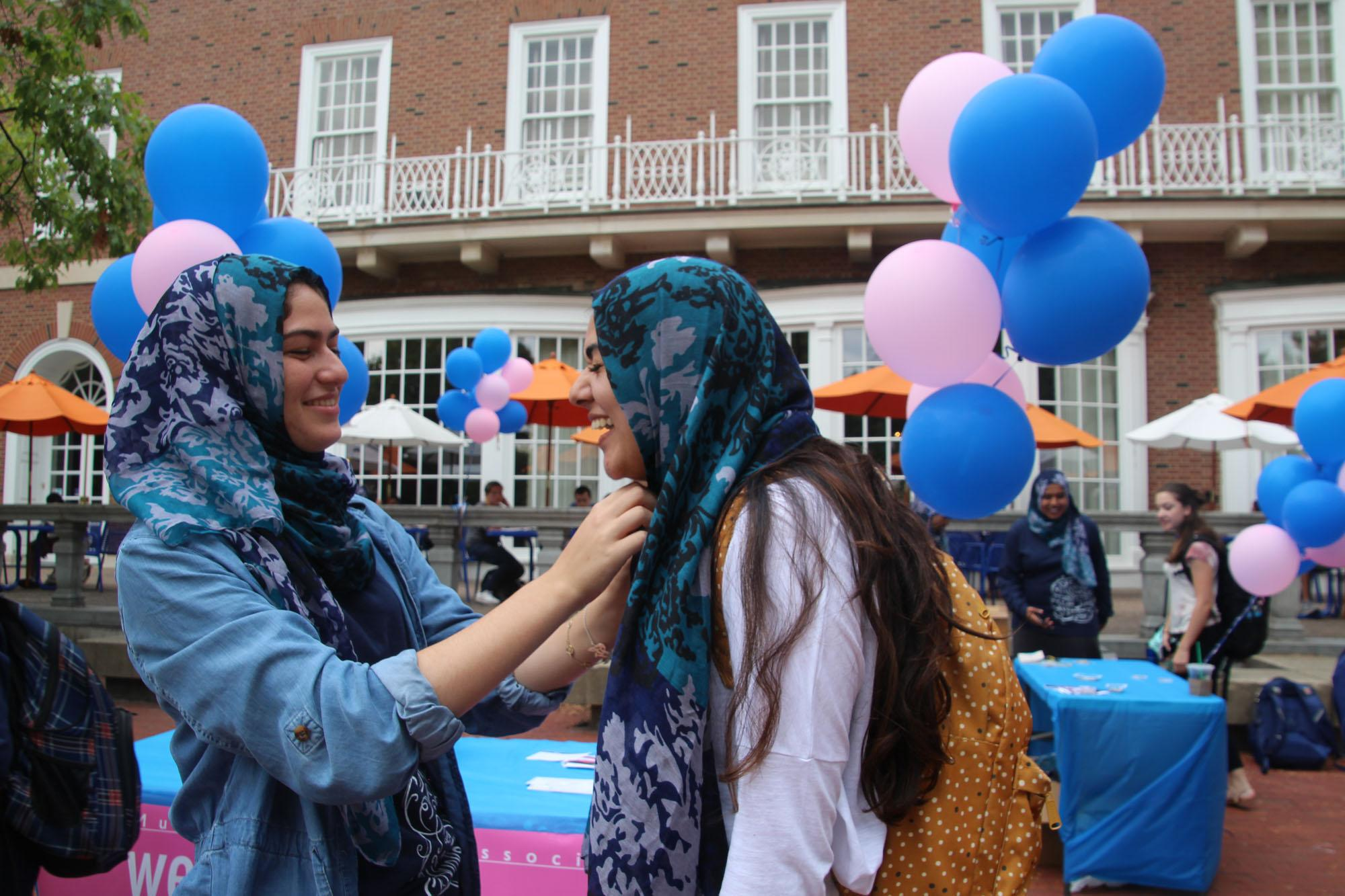 Reema Ghabra, sophomore in LAS, puts a hijab on Aisha Motan, a freshman in Education, as part of the Wear a Hijab Challenge, an event during Islam Awareness Week on Monday.