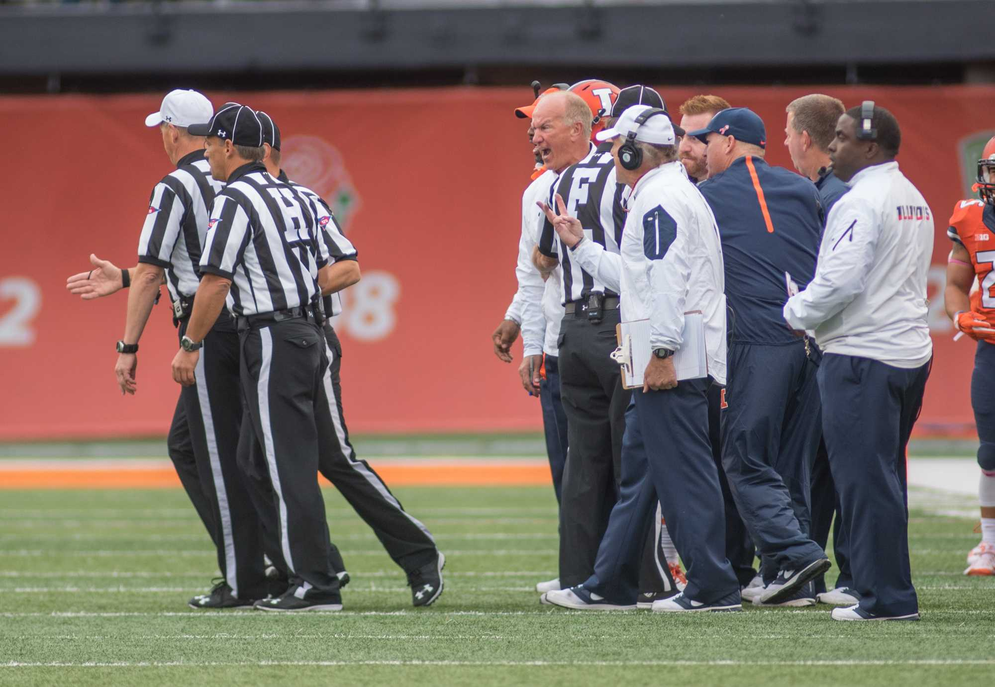 Head coach Bill Cubit disagrees with a call and has to be held back while he screams at the referees during Illinois' 14-13 win over Nebraska on Saturday at Memorial Stadium.