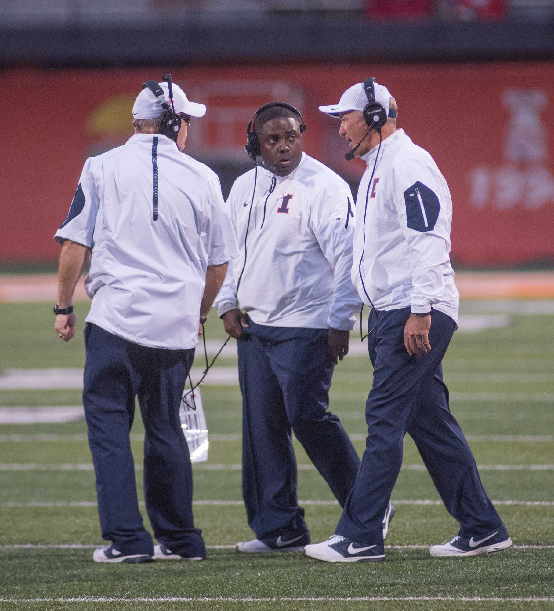 Illinois coaches Mike Ward (left), Tim Banks (center) and Bill Cubit converse on the field during Saturday's game against Nebraska at Memorial Stadium. Illinois won 14-13.
