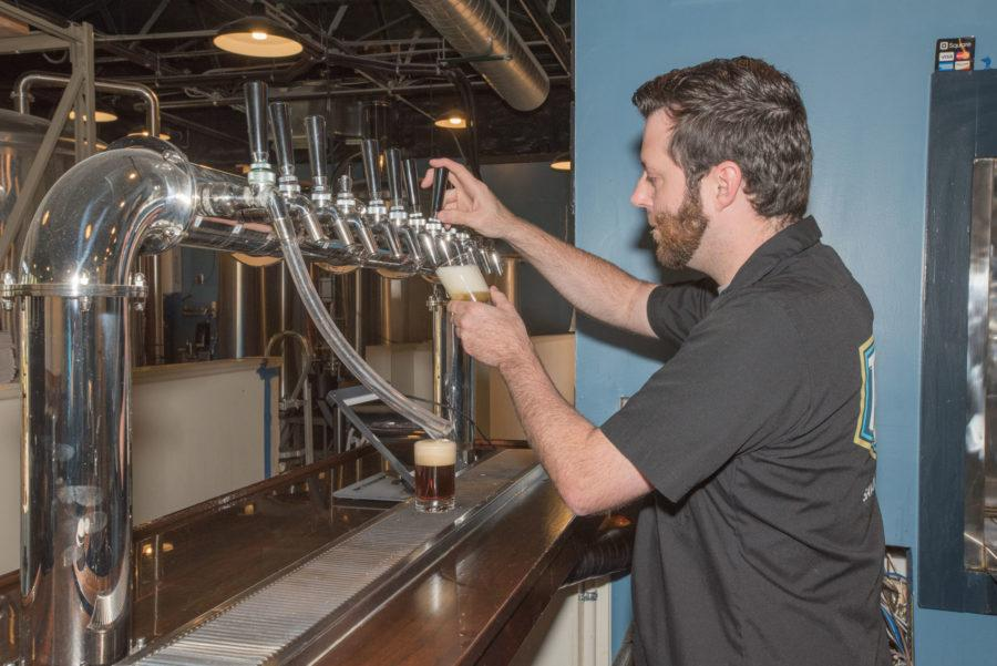 Michael Miller, Triptych brewery's sales representative pours a taster glass of their special Pygmalion Pilsner created for the Pygmalion Festival in Champaign-Urbana that happened last month.