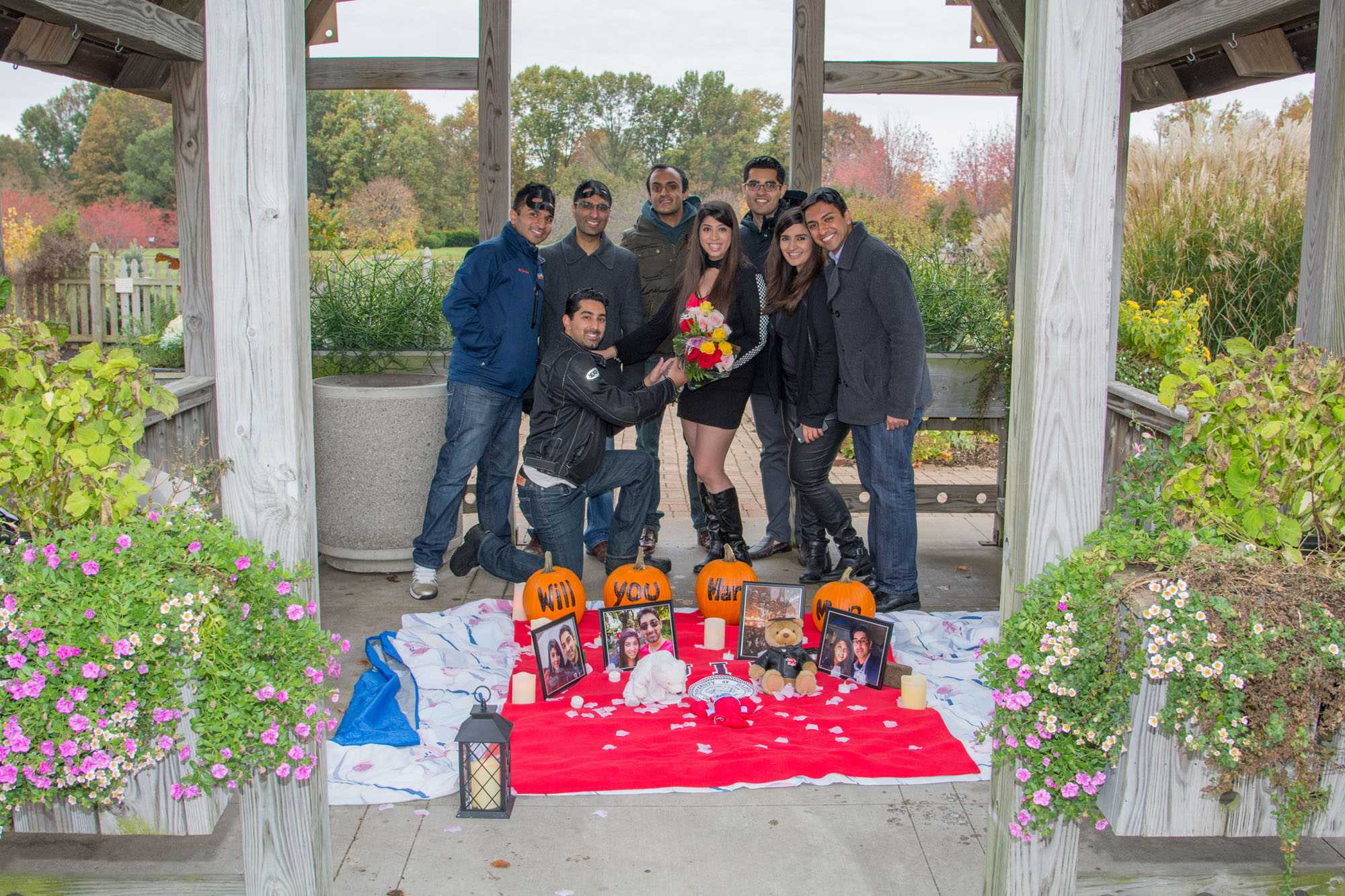 (kneeling) Ahmed Hussain, 2009 graduate of the College of Business, his fiance (with flowers) Munira Charania, a first year MBA student, and their friends and family pose together in the Idea Garden at the Arboretum on Saturday, Oct. 31 after Hussain proposed to Charania.