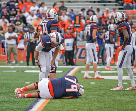Back up quarterback Chayce Crouch leans down to check on injured lineman Zach Heath during the game against Western Illinois at Memorial Stadium on Saturday, Sept. 12.