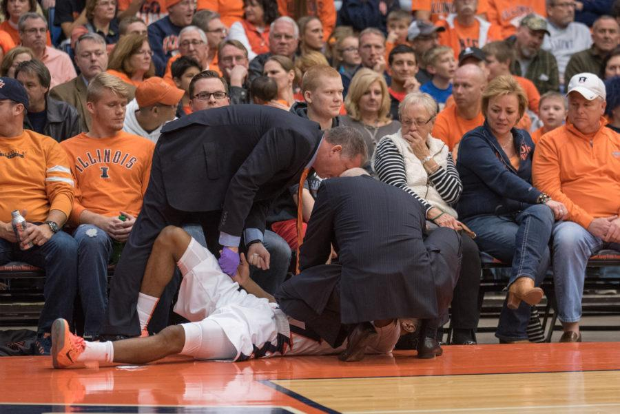 Jalen Tate lies on the ground injured and is tended to by the trainer and head coach during the game againstNorthern Florida at Prairie Capitol Convention Center on Friday.