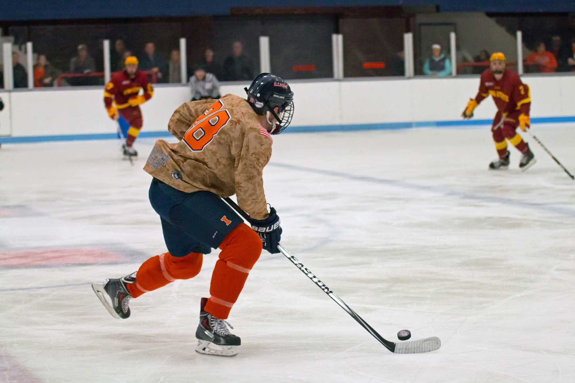 Aaron Dusek carries the puck up the ice during the game at the Ice Arena against Iowa State on Friday, November 13. Illinois won 4-3 in a shootout.