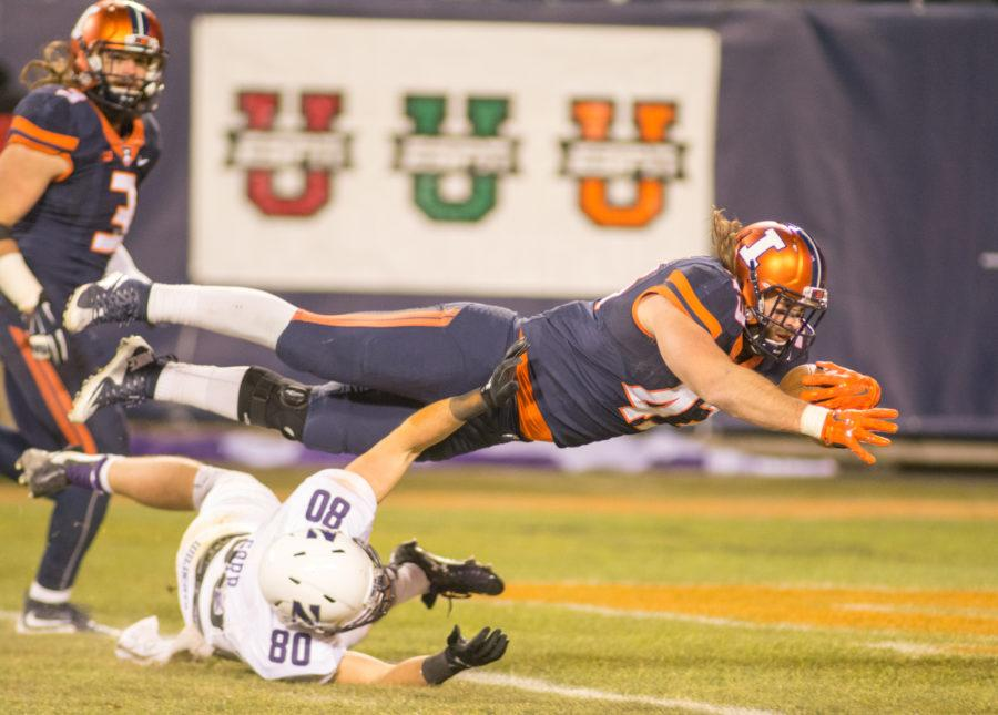Linebacker Mason Monheim dives over the goal line to return an interception for a touchdown during the game against Northwestern at Soldier Field on Saturday. Illinois lost 24-14.