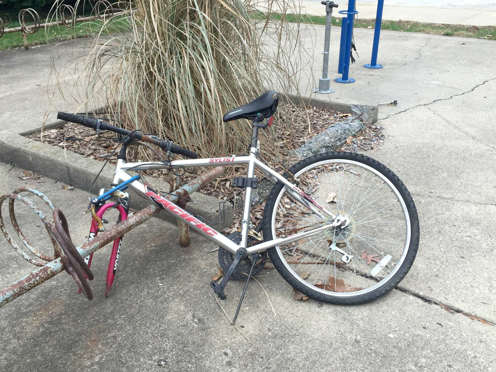 A bike locked on the rack north of the Henry Administration Building has rusted gears and handlebars and is missing a wheel. Parking department employees tag bikes like these before taking them to the Campus Bike Center.