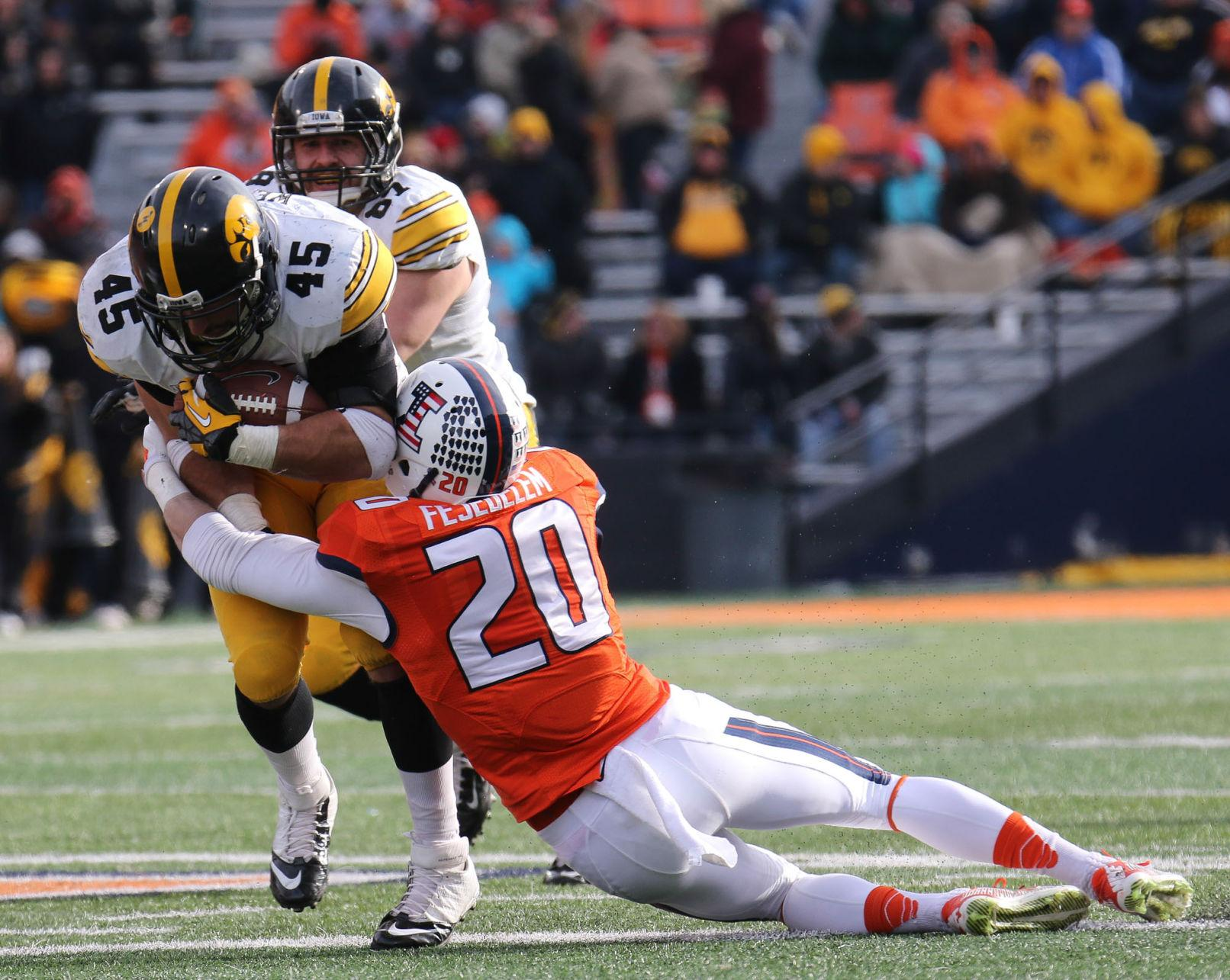 Illinois' Clayton Fejedelem (20) tackles Iowa's Mark Weisman (45) during the game against Iowa at Memorial Stadium, on Saturday, Nov. 15, 2014. The Illini lost 30-14.