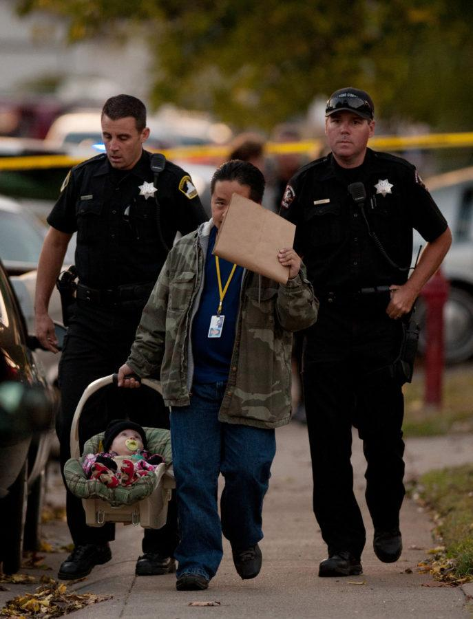 A member of child protection services carries an unharmed 6-month-old boy found at the scene of a triple homicide in a duplex in Rancho Cordova, California, on Tuesday, October 23, 2012. Sacramento County Sheriff's Department officials confirmed that three bodies were found, that of a woman, described as being in her 20s, and her two children -- a girl, 3, and a boy, 2 -- dead in one room. The 6-month-old boy was found crying but unharmed in another room. (Jose Luis Villegas/Sacramento Bee/MCT)