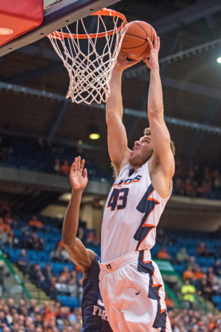 Forward Michael Finke jumps to dump the ball during the game against North Florida at the Prairie Capitol Convention Center on Friday, Nov. 13. Illinois lost 93-81.