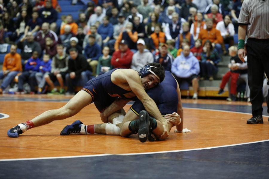 Illinois' Caleb Ervin wrestles Michigan's Eric Grajales at Huff Hall on Friday, Jan. 18, 2014.