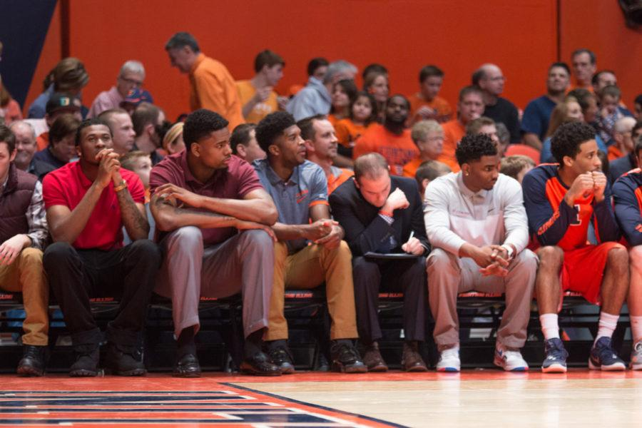 Illini players (from left) Leron Black, Mike Thorne Jr., Kipper Nichols and Tracy Abrams, along with graduate manager James Haring (in suit) watch the action during Illinois' 78-68 loss to Michigan at State Farm Center on Wednesday.