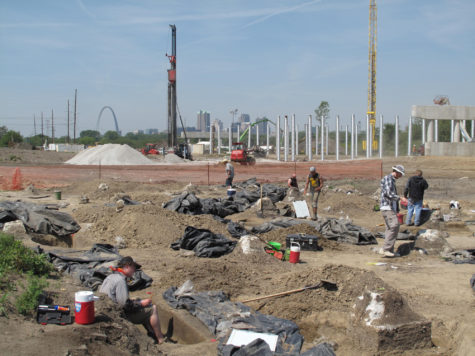 The University excavation crew works at the dig site while the St. Louis skyline looms in background.