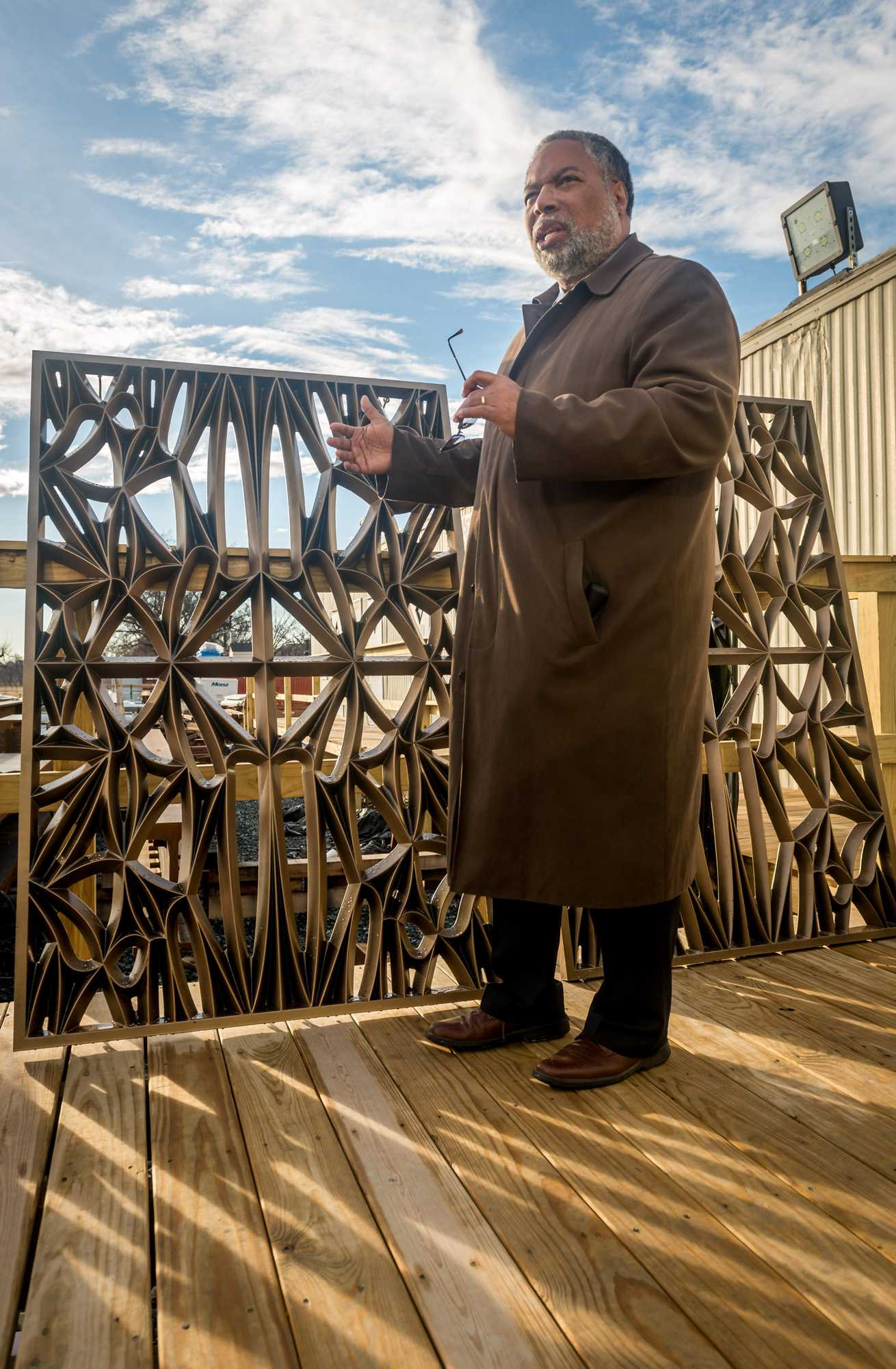 Director of the Smithsonian Institute National Museum of African American History and Culture Lonnie Bunch III talks about the design of the bronze plated aluminum panels which will comprise the bronze and glass-panel façade, known as the Corona, during a tour of the museum construction site at 14th St. NW and Constitution Avenue in Washington, D.C. on Feb. 21, 2014. The Corona is a representation of traditional African architecture using modern materials and will visually define the museum. The Corona will hang from the top of the museum with no intermediate support on the side of building.