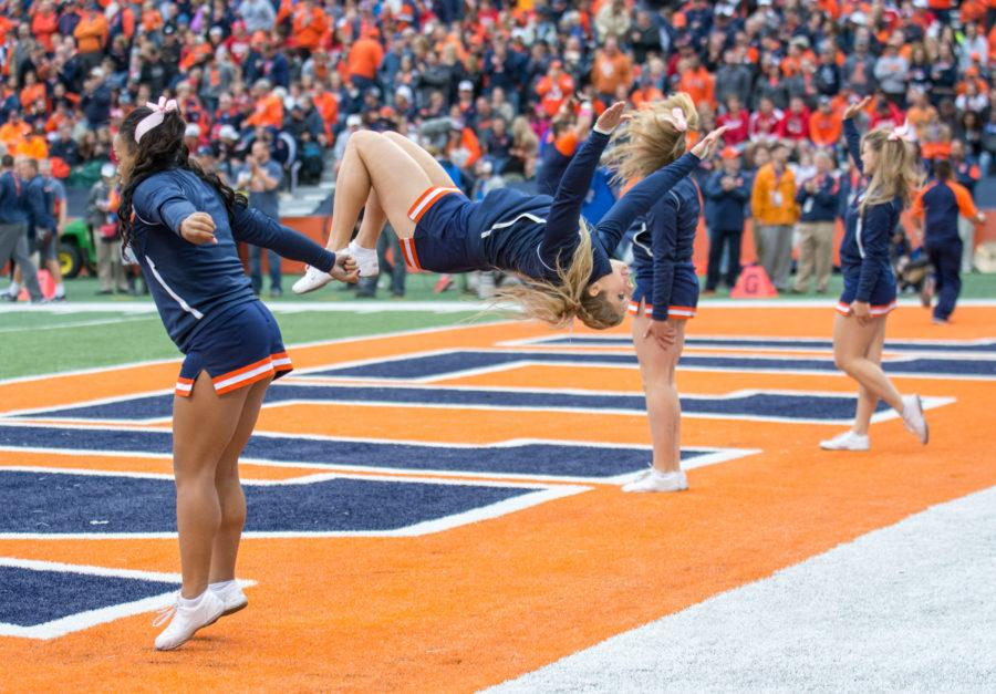 Illini cheerleaders flip after an Illinois score during the Homecoming game against Wisconsin at Memorial Stadium on Saturday, October 24. Illinois lost 13-24.