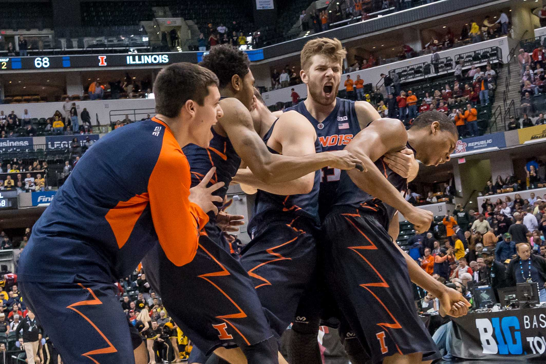 Illinois' Michael Finke hugs Maverick Morgan and Malcolm Hill after defeating Iowa in the second round of the Big Ten Tournament in Indianapolis, Indiana on March 10. The Illini won 68-66.