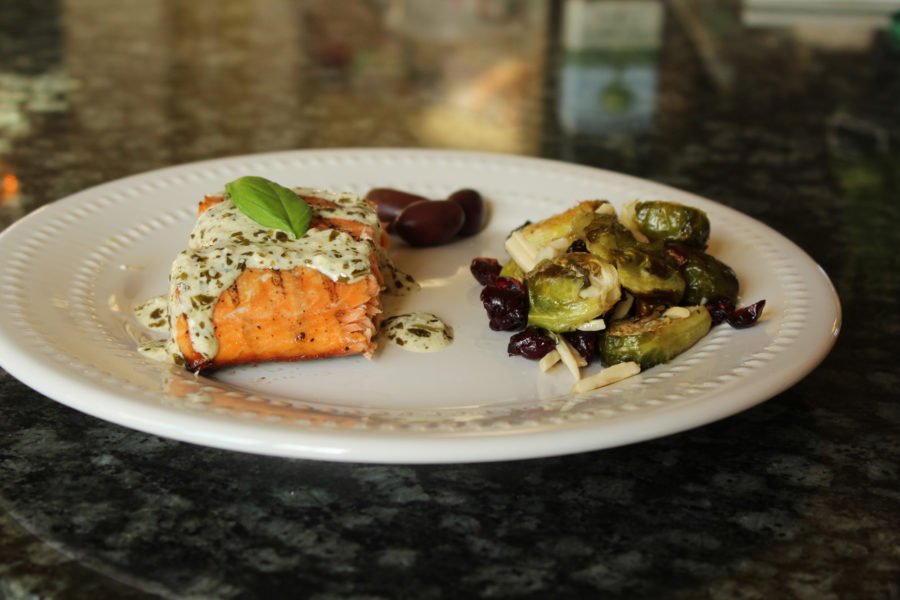 A pesto sauce is drizzled over salmon fillets and served with roasted brussels sprouts.