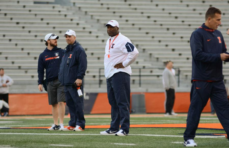 Illinois' football headcoach Lovie Smith obverses the players running drills during the first spring practice on Friday, April 1, 2016.