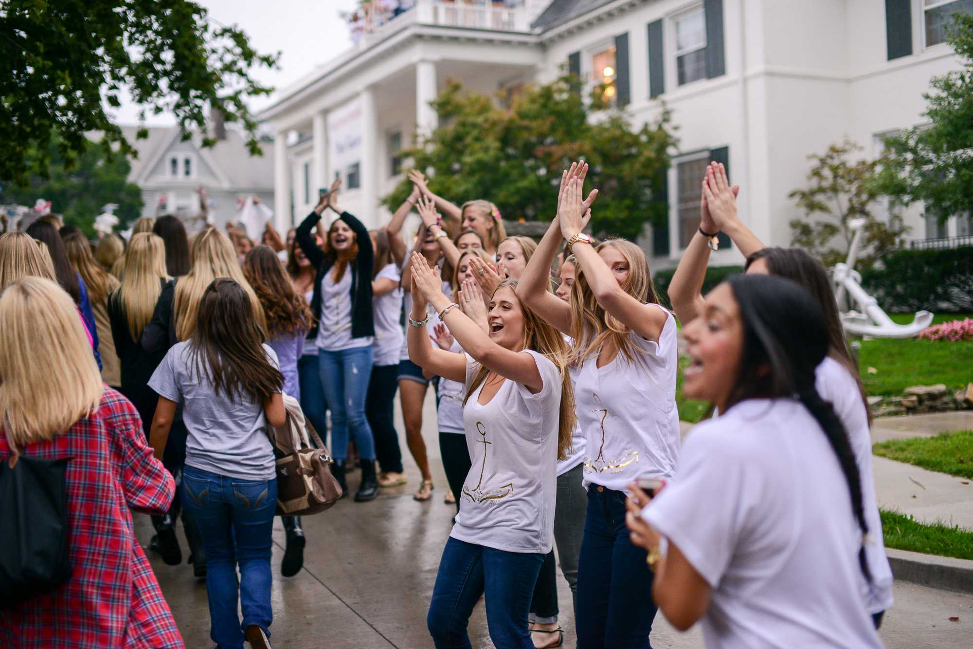 These sisters form a triangle with their arms and hands, showing sorority pride during Bid Day on Monday, Sept. 15, 2014.