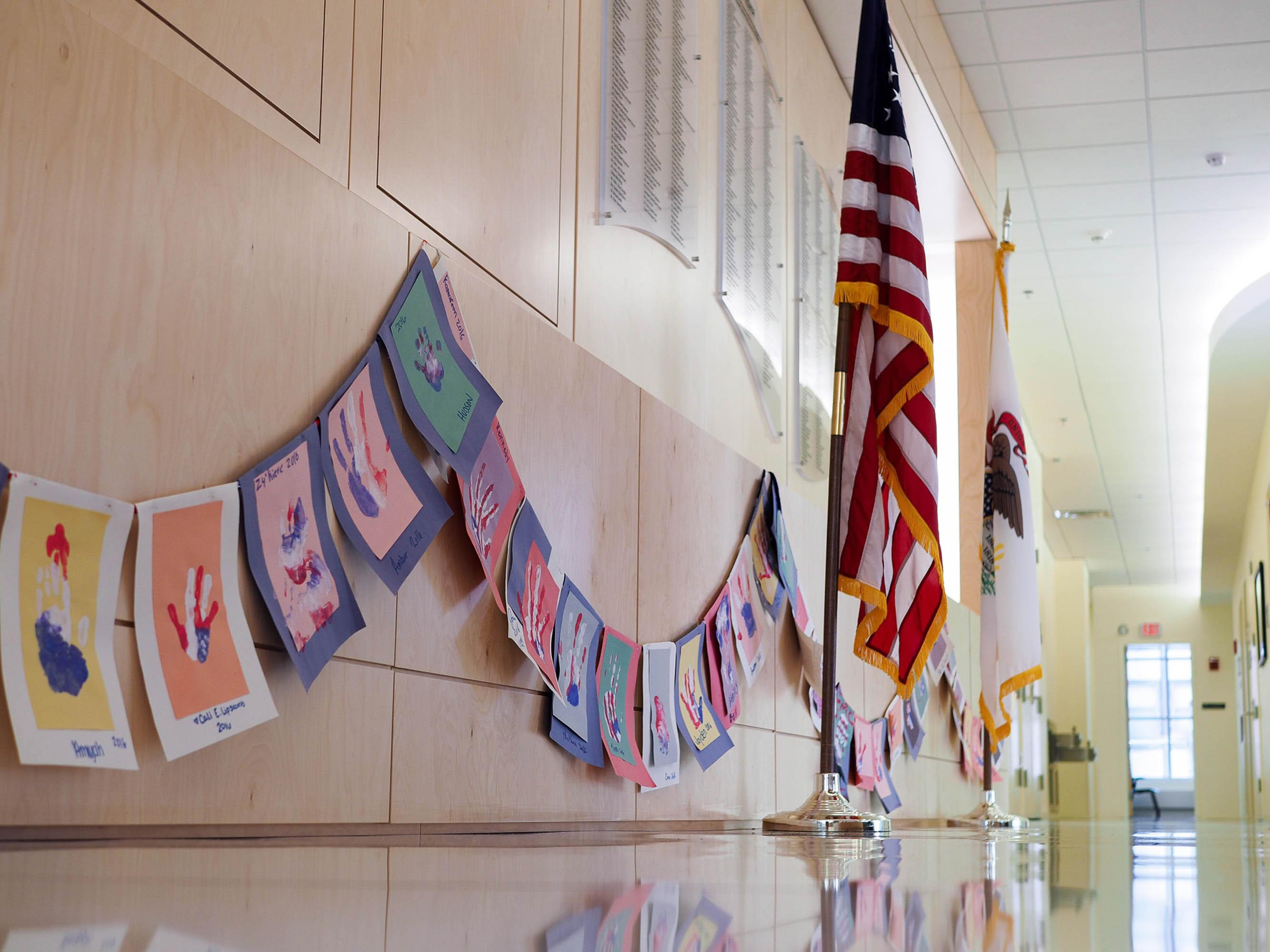 The Veteran and United States Flag flank the Wall Of Honor found in the entrance of the Center for Wounded Veterans in Higher Education in Urbana, IL. August 16, 2016.