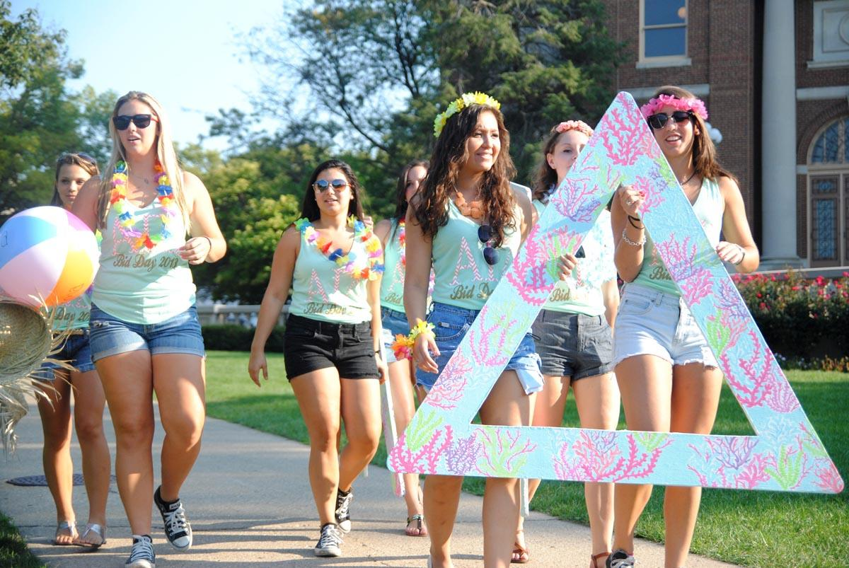 Alpha Gamma Delta sorority members arrive on the Quad to welcome their new pledge class.