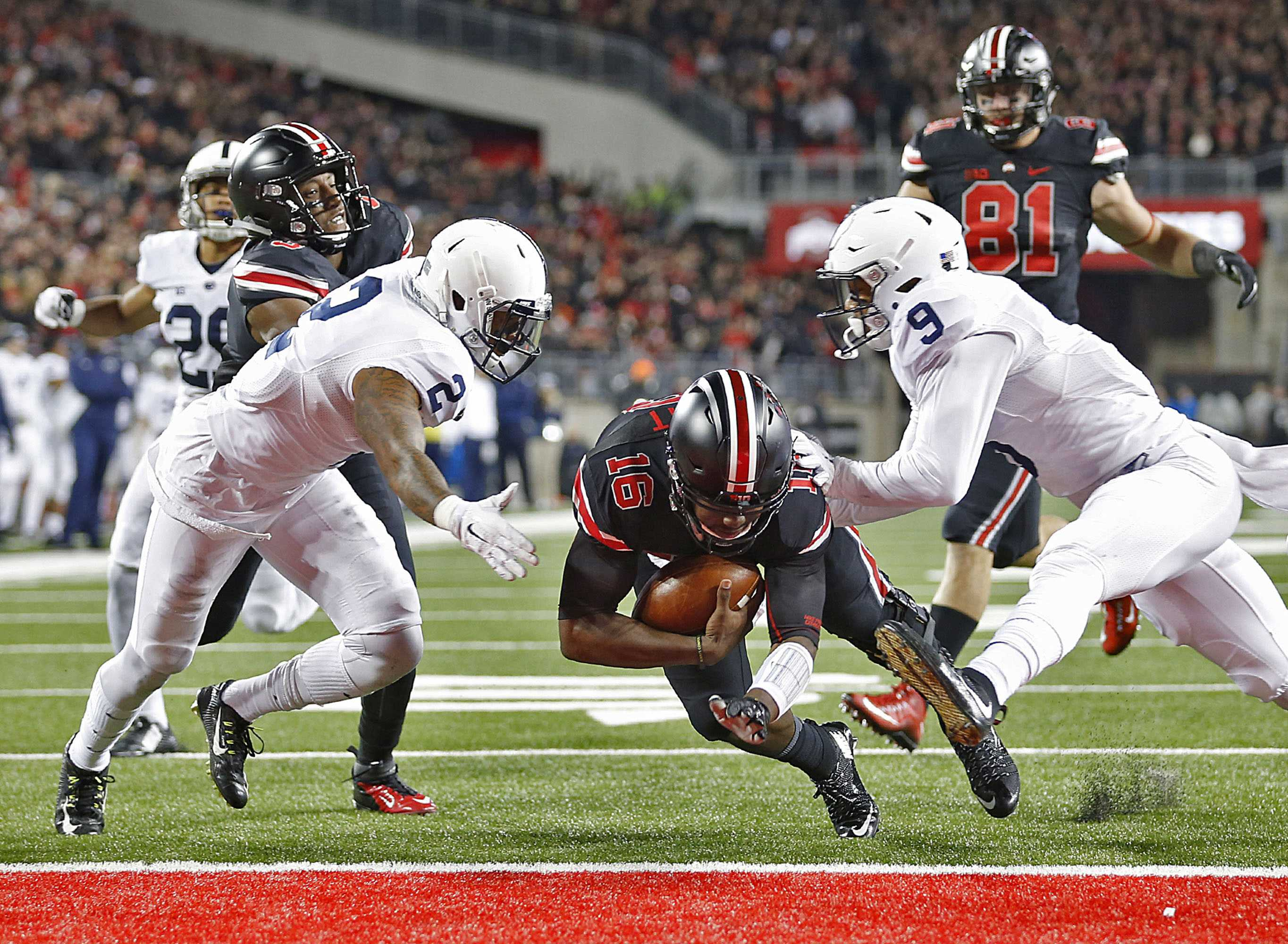 Ohio State quarterback J.T. Barrett (16) slides between Penn State safeties Jordan Lucas (9) and Marcus Allen (2) for a second-quarter touchdown at Ohio Stadium in Columbus, Ohio, on Saturday, Oct. 17, 2015.