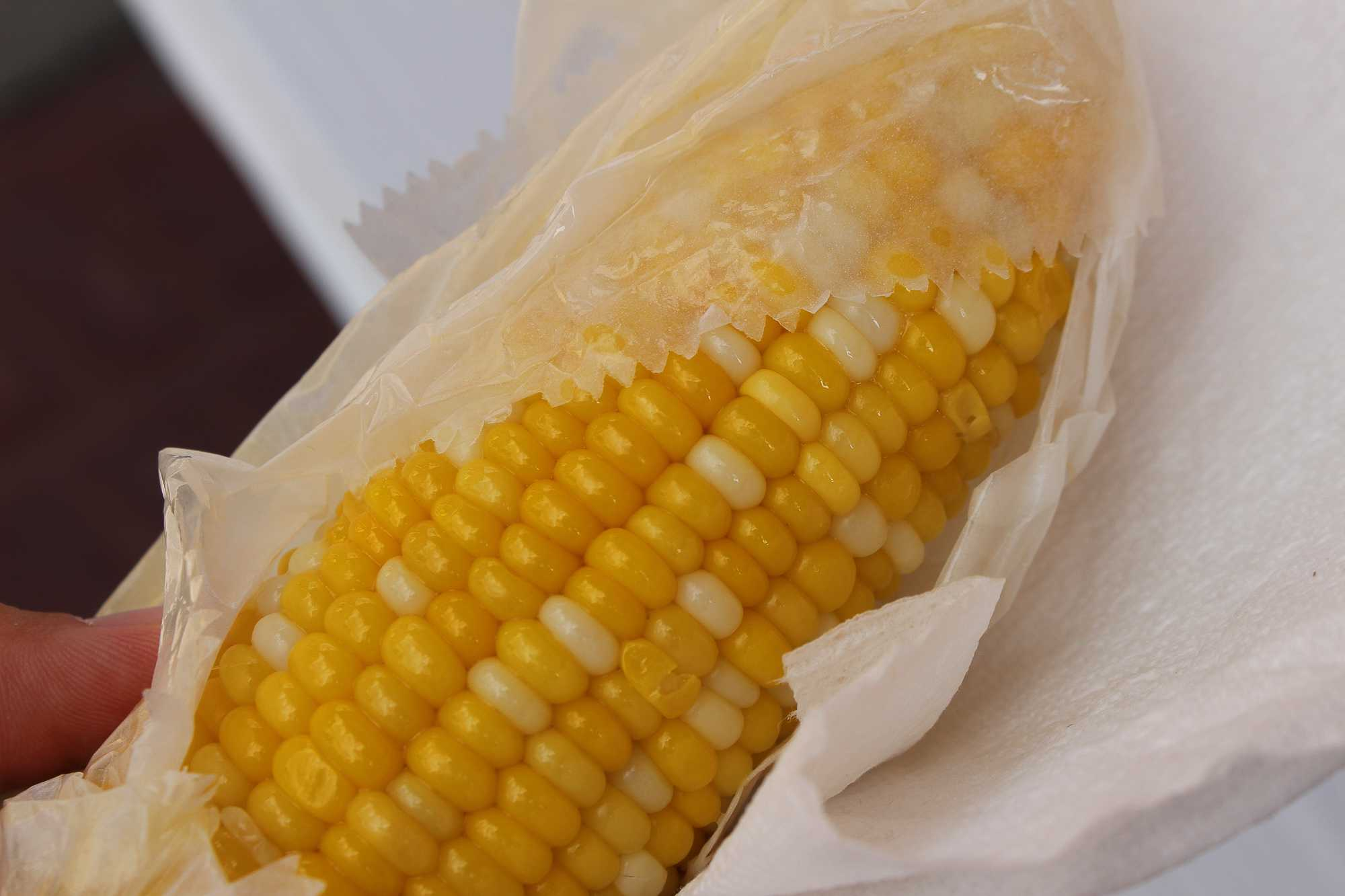 A corn on the cob is unwrapped ready to be eaten at the Urbana Sweetcorn Festival in downtown Urbana on Saturday, Aug. 27