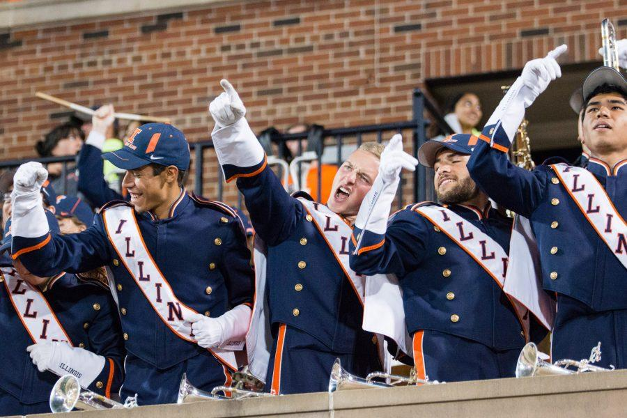 Members of the Marching Illini cheer on the Illini during the game against North Carolina at Memorial Stadium on Saturday. The Illini lost 48-23.