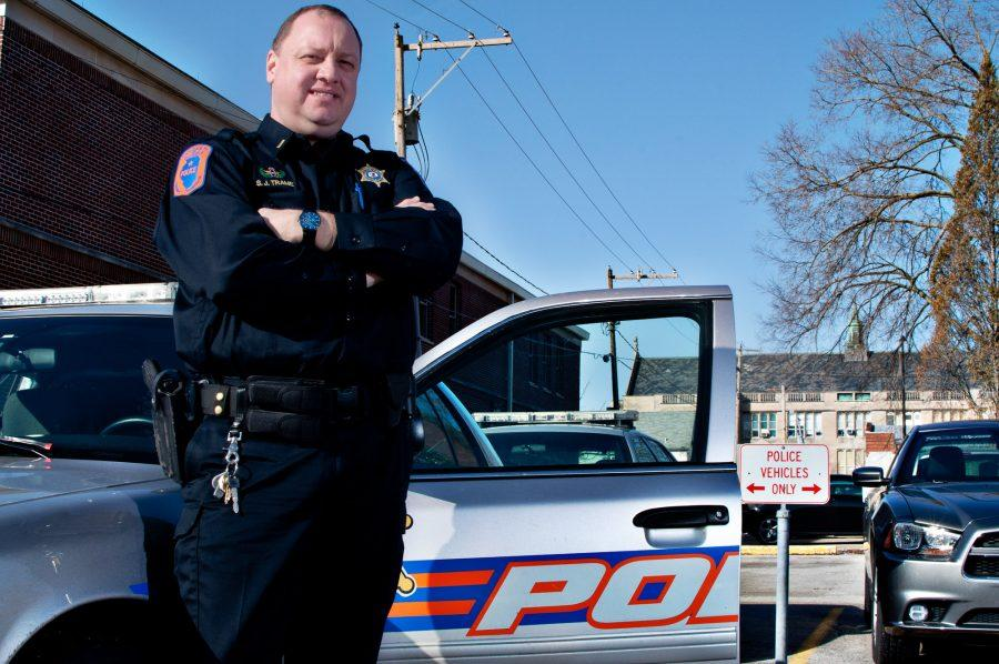 A police officer of the University Police Department stands in front of a squad car.
