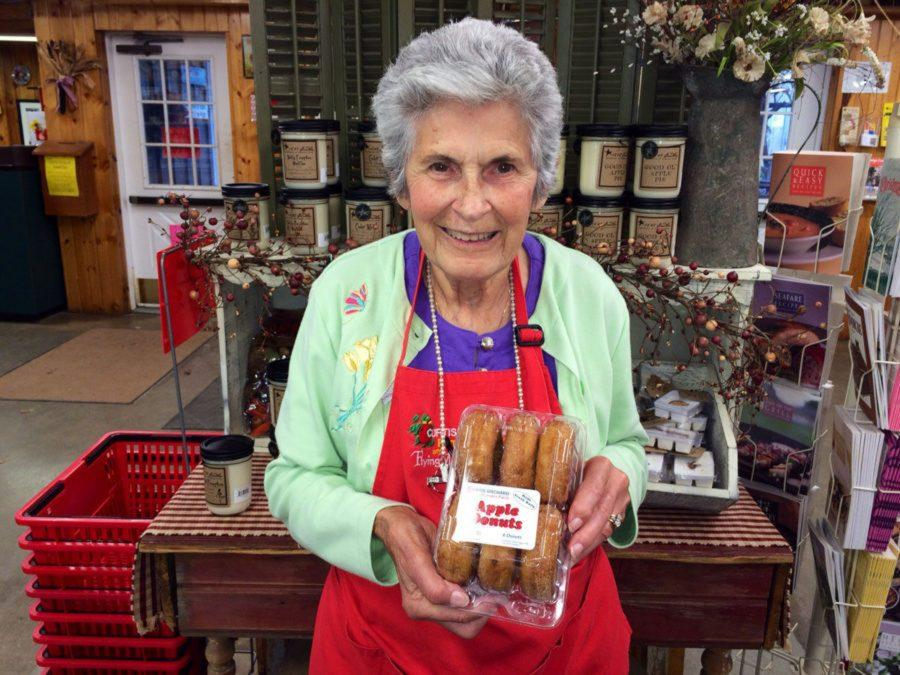 Joyce+Curtis+stands+in+the+shop%2C+holding+a+box+of+apple+donuts.+Curtis+was+a+mainstay+in+the+C-U+community.