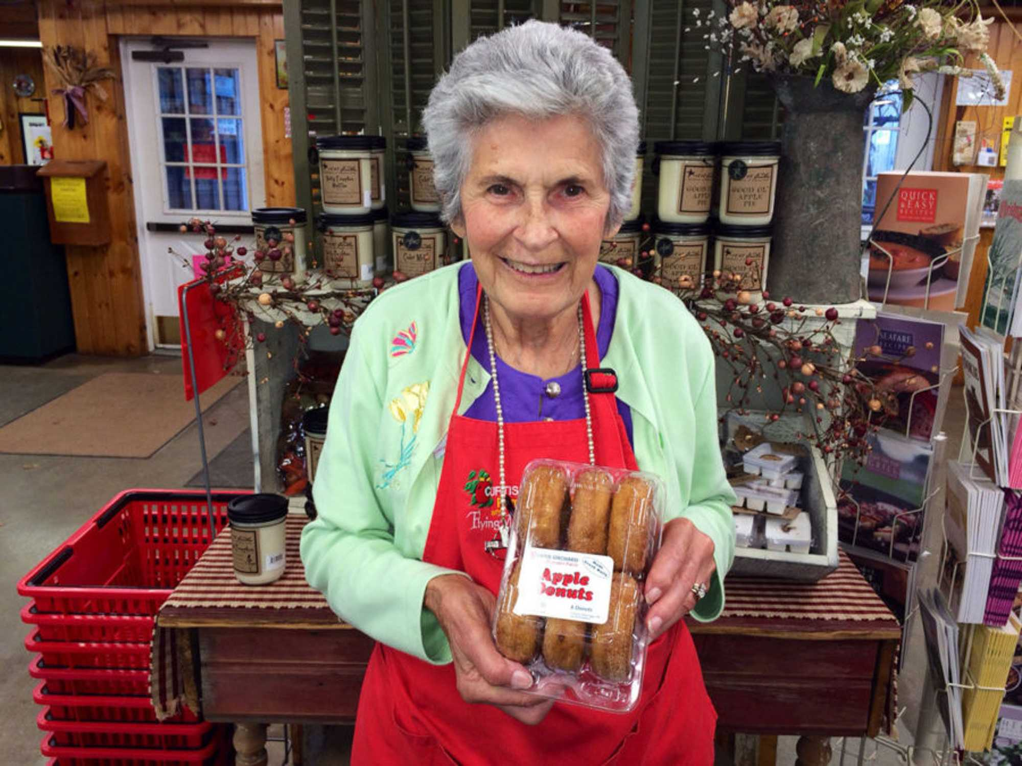 Joyce Curtis stands in the shop, holding a box of apple donuts. Curtis was a mainstay in the C-U community.