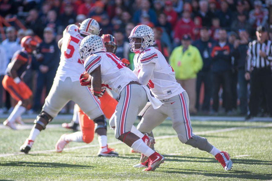 Ohio State quarterback J.T. Barrett hands the ball off to running back Ezekiel Elliott during the game against Illinois at Memorial Stadium on Saturday, Nov. 14. Illinois lost 28-3.