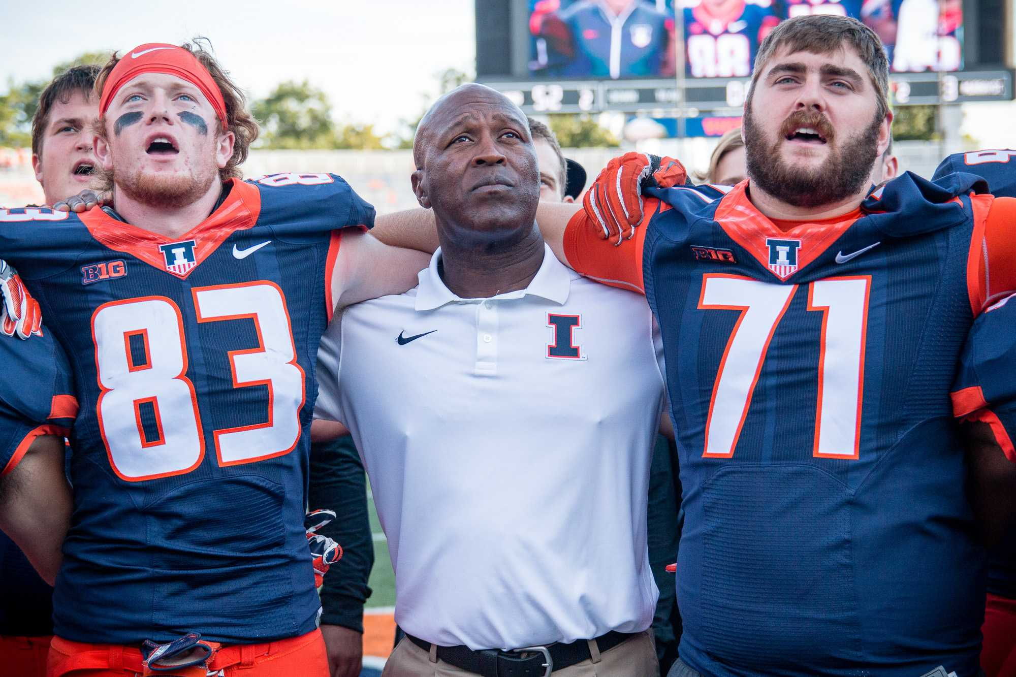 Illinois head football coach Lovie Smith (center) joins tight end Bobby Walker (83) and offensive lineman Joe Spencer (71) in singing Hail to the Orange after the game against Murrary State at Memorial Stadium on Saturday, September 3. The Illini won 52-3.