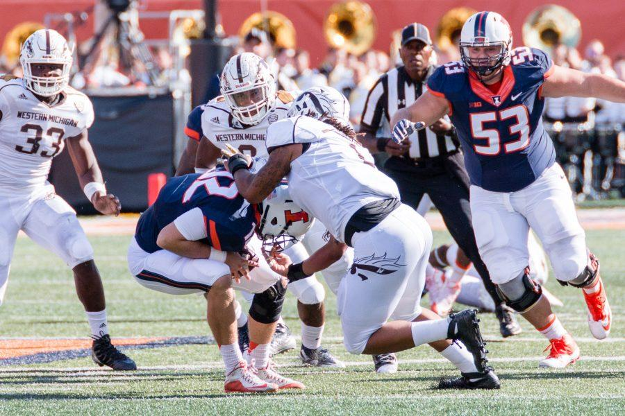Western Michigan defensive end Keion Adams (right) sacks Illinois quarterback Wes Lunt (12) during the game at Memorial Stadium on September 17. The Illini lost 34-10.