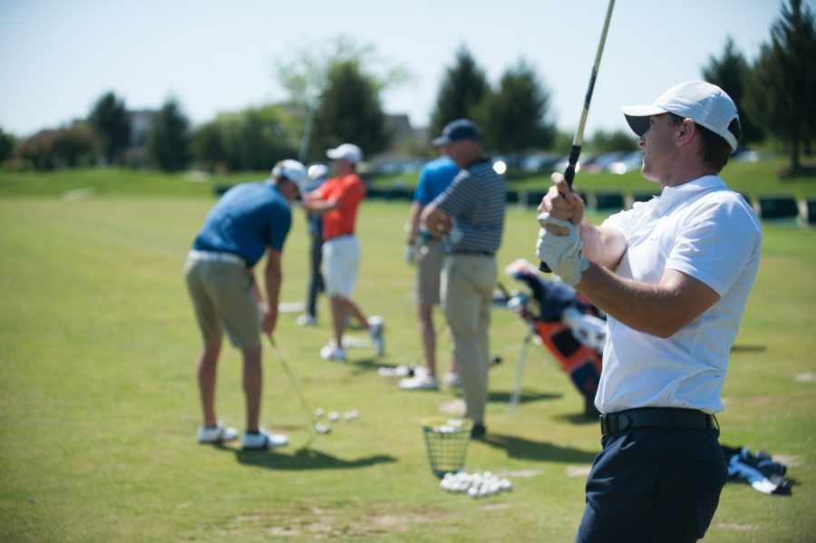 Illinois' Luke Guthrie and other members of the Illinois team practice at the driving range at Stone Creek Golf Club in Urbana on Wednesday, April 18, 2012.