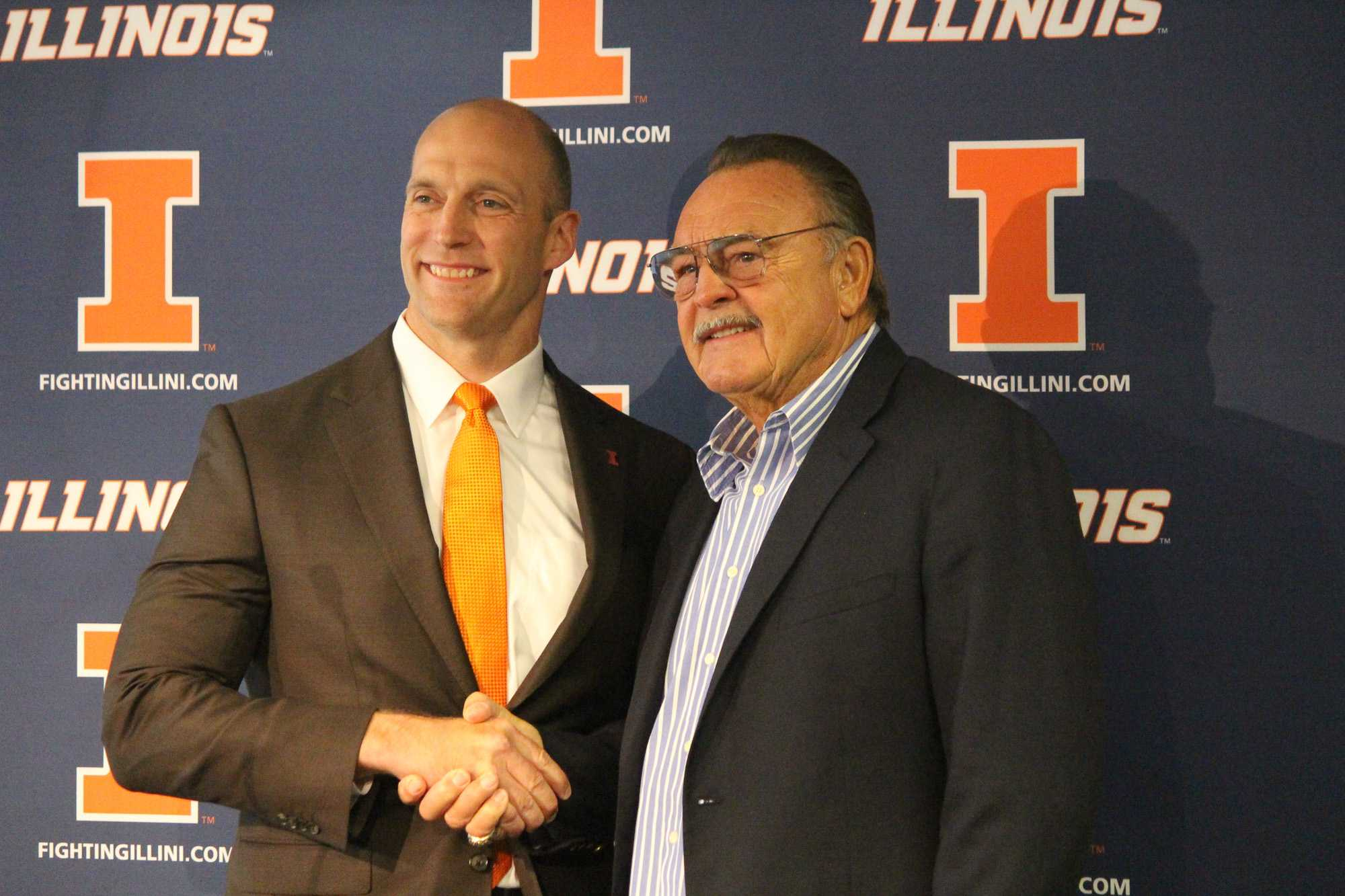 Honoree Dick Butkus shakes hands with Athletic Director Josh Whitman at Memorial Stadium on Thursday.