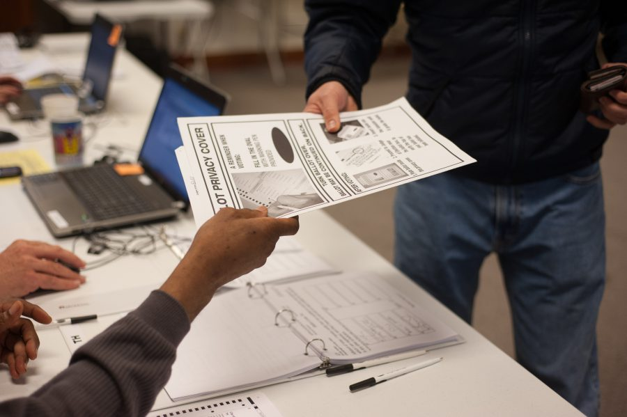 An election judge hands a ballot to a voter at the Salvation Army in Champaign, on election day, Tuesday, Nov. 6, 2012.