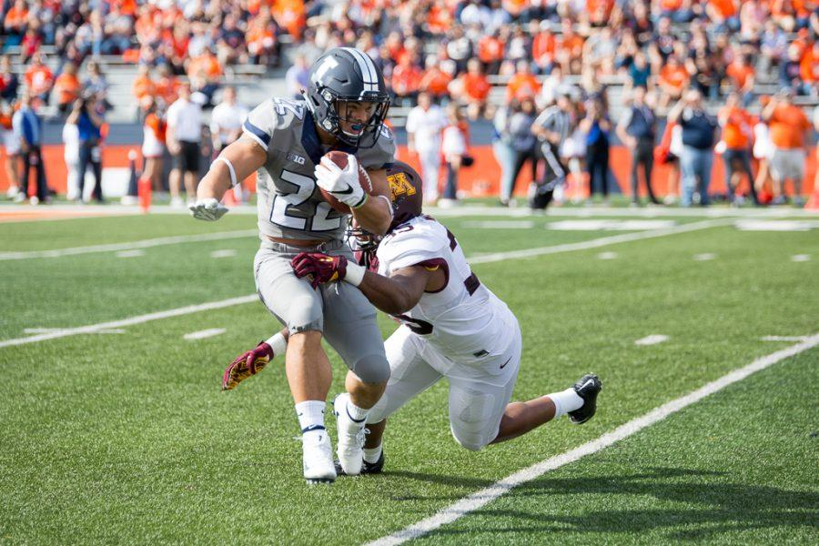 Illinois running back Kendrick Foster (22) tries to break a tackle on a kick return during the first half of the game against Minnesota at Memorial Stadium on Saturday October 29. The Illini are losing 14-7 at half.
