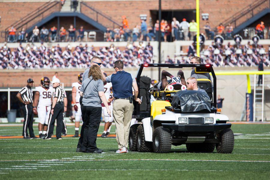 Illinois wide receiver Malik Turner (11) holds onto his head while being carted off the field after an injury during the first half of the game against Minnesota at Memorial Stadium on Saturday October 29. The Illini are losing 14-7 at half.